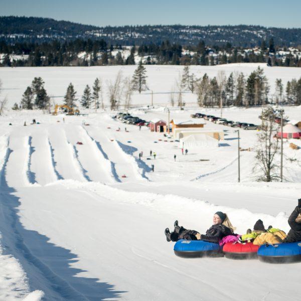 three snowtubers descend hill