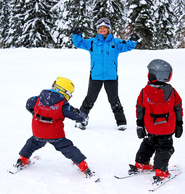 Instructor Smiles While Teaching Youngsters to Ski