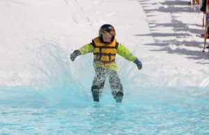 child crosses pond during skimming competition