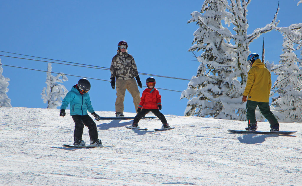 Family of Four skis under bear chair lift