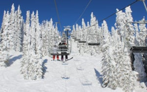 Skiers ride Lakeview lift on sunny day with snow packed into trees