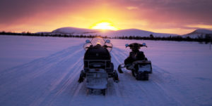 snowmobiles with sunset in background