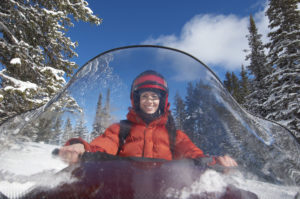 Woman smiles while snowmobiling