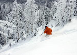 skier skis away in powder
