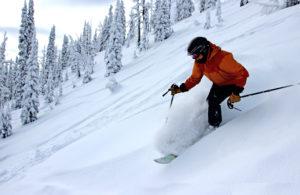 woman skis steep powder