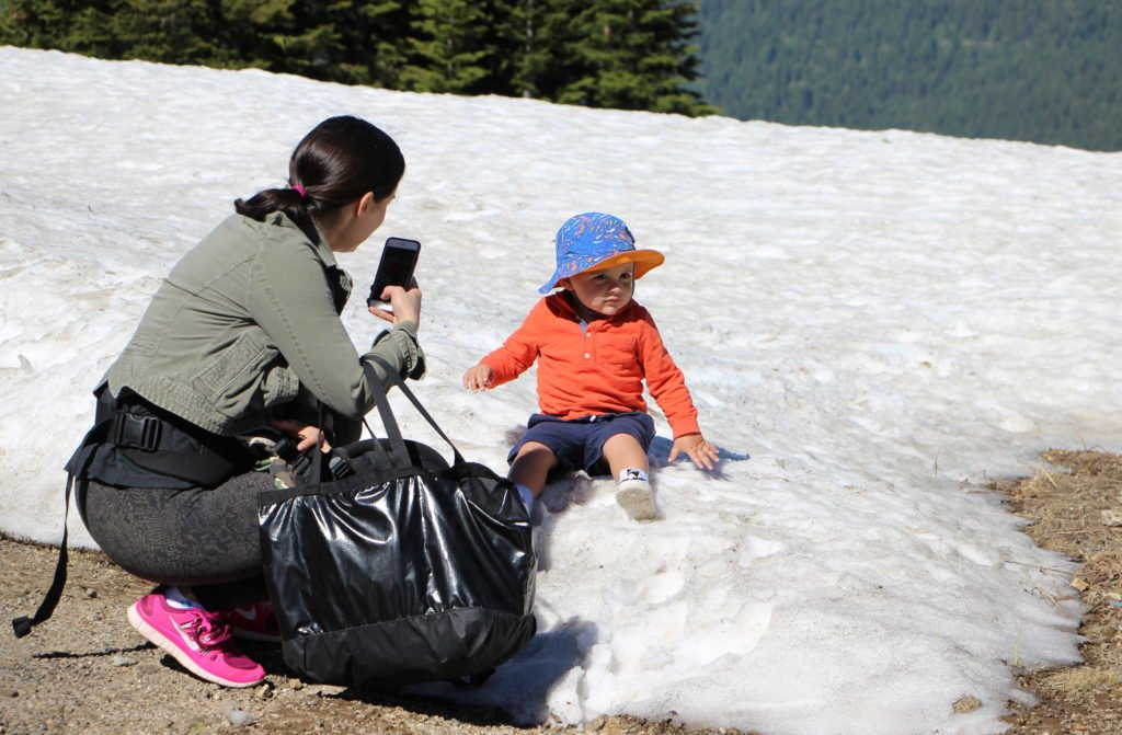 Mom photographs baby sitting on snowbank