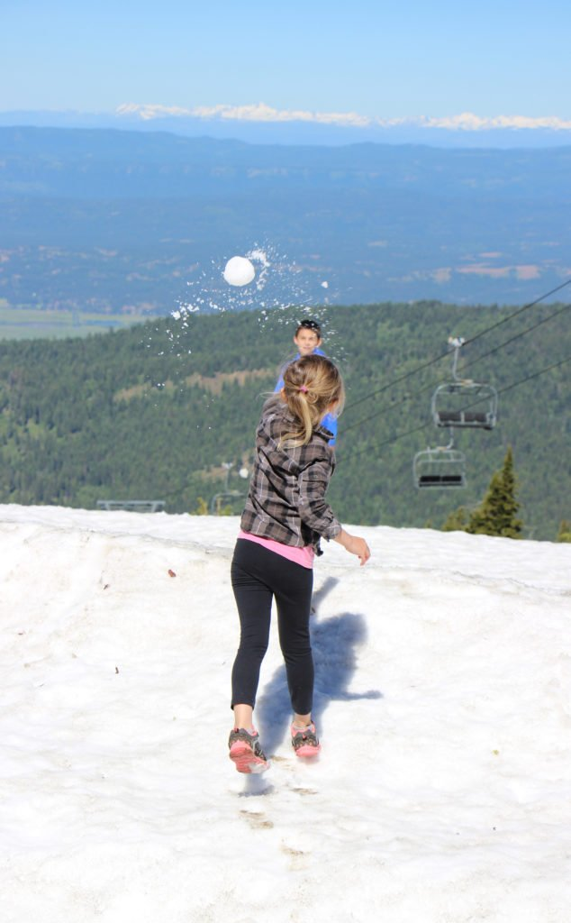 girl tosses a snowball on the summit