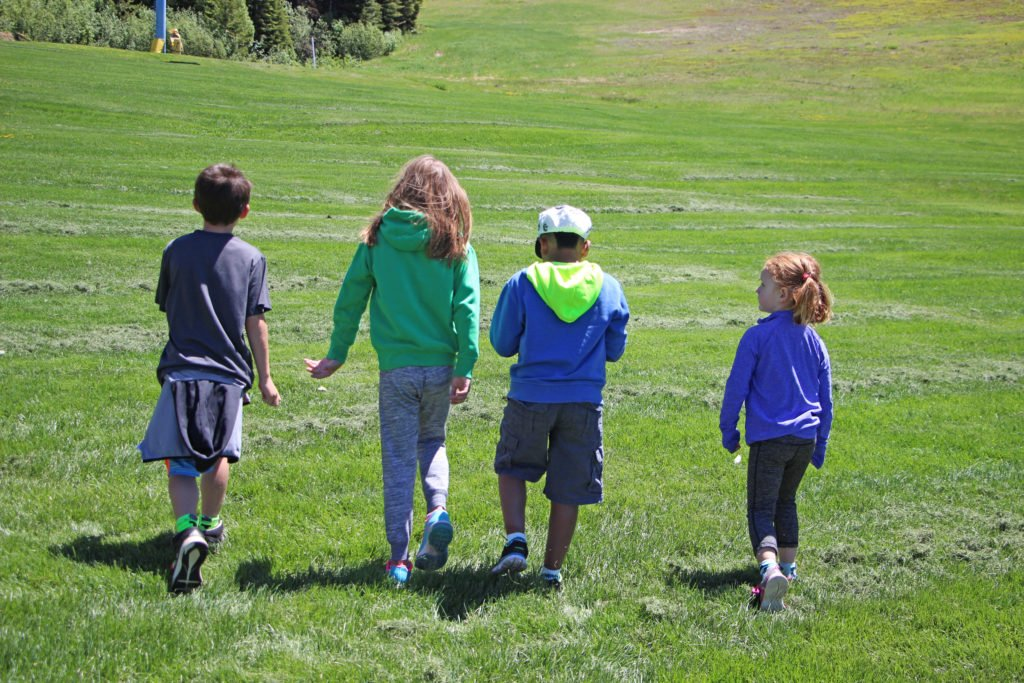 four kids walk on grass