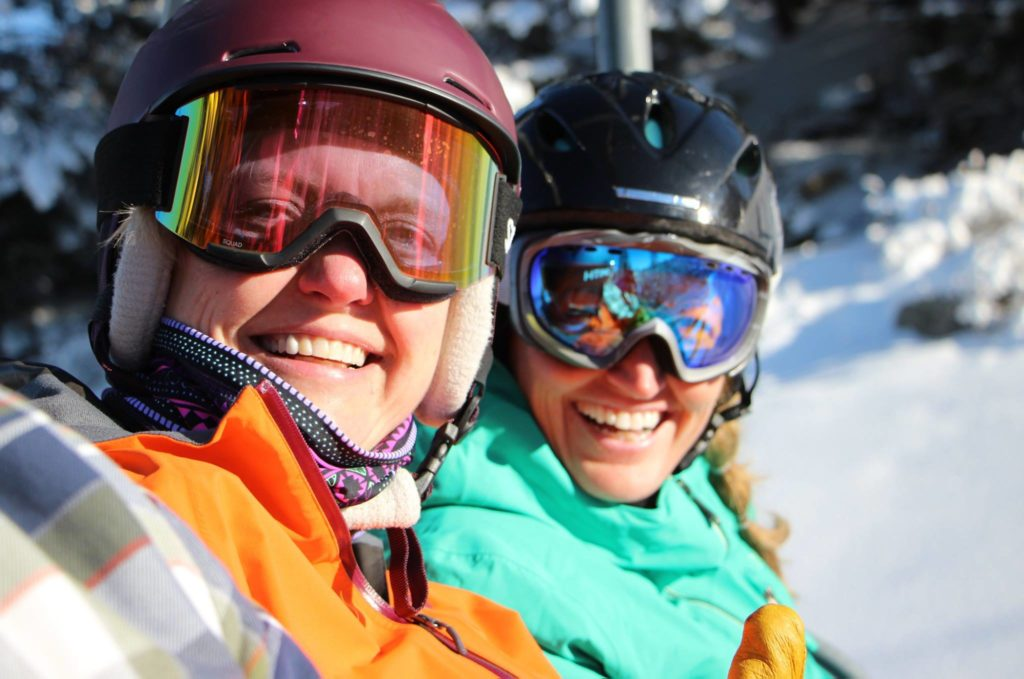 Women smile on chairlift
