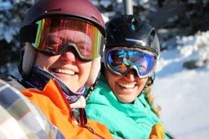 Women smile on chairlift